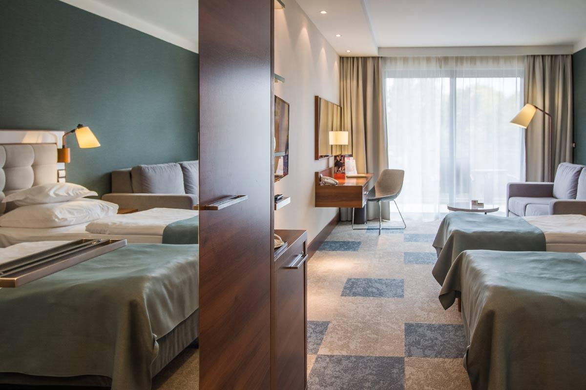 odbicie w lustrze łóżek pokoju hotelowego