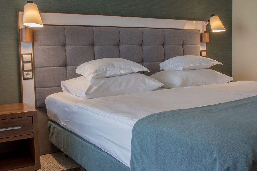 wygodne łózko w hotelowym pokoju